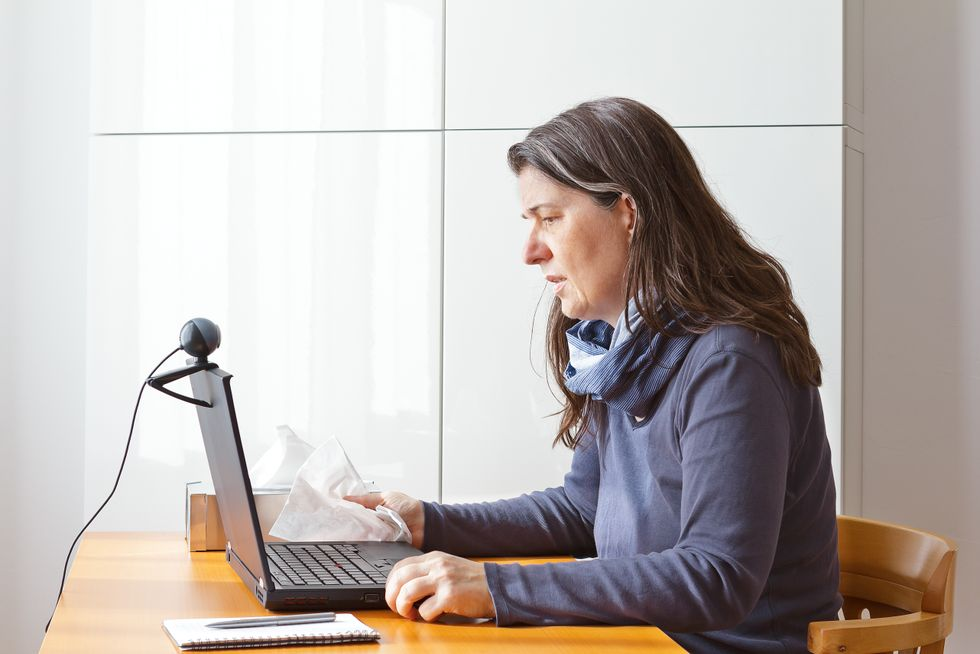 Video consult: woman with a cold calling her doctor on a laptop via video link.
