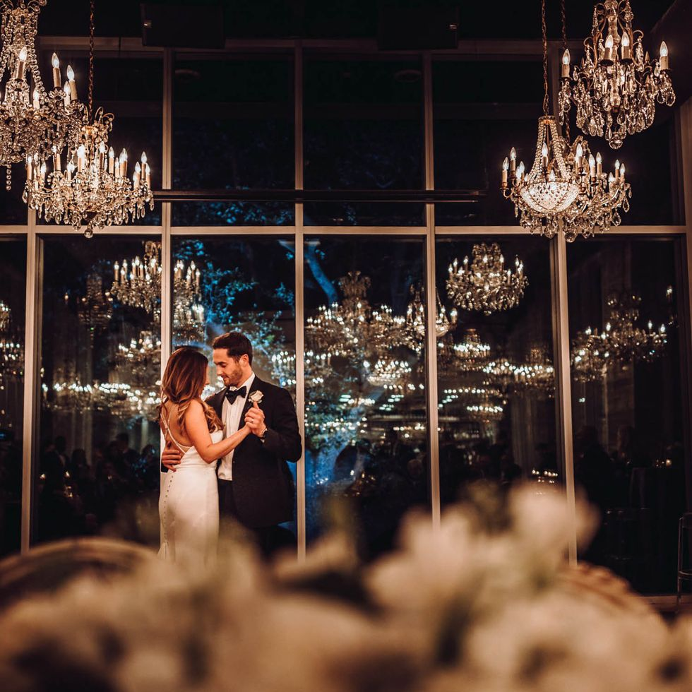 "The newly minted Almquists savor a romantic and intimate ""last dance"" amid the chandeliers at the end of their reception."